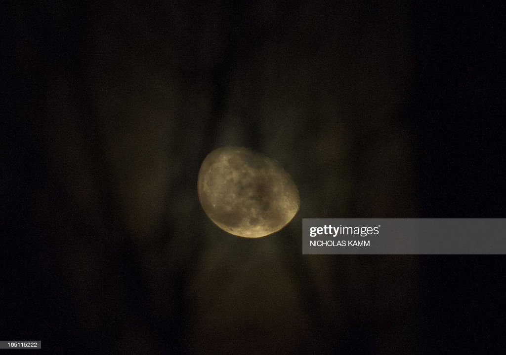 An oblong moon appears above Washington early on March 31, 2013. AFP PHOTO/Nicholas KAMM