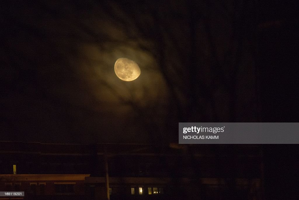 An oblong moon appears low above a residence in Washington early on March 31, 2013. AFP PHOTO/Nicholas KAMM