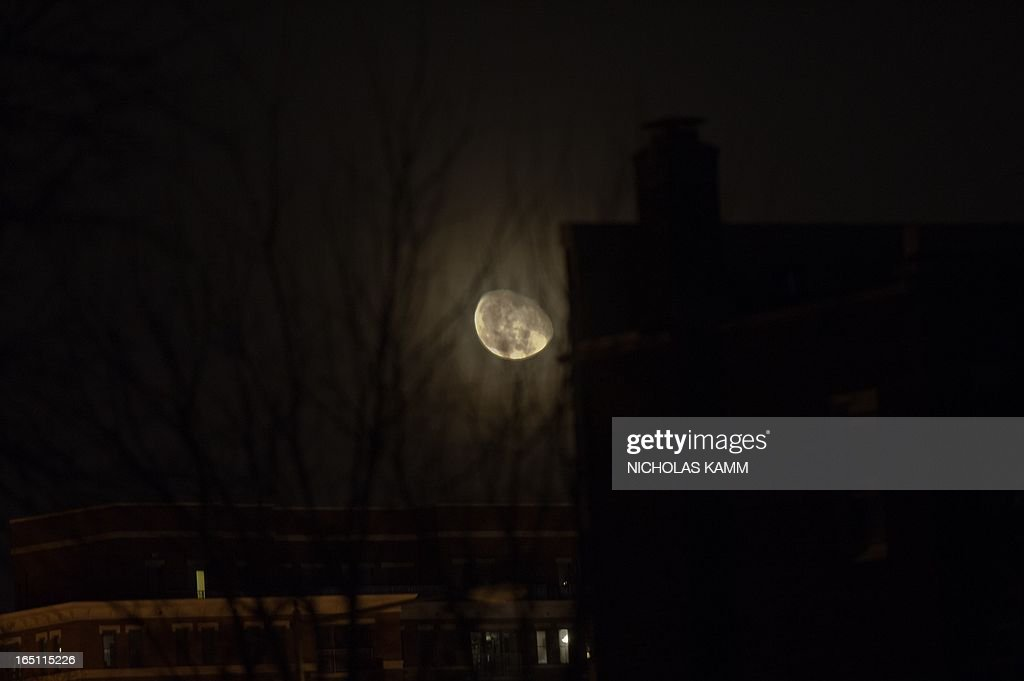 An oblong moon appears low above residences in Washington early on March 31, 2013. AFP PHOTO/Nicholas KAMM
