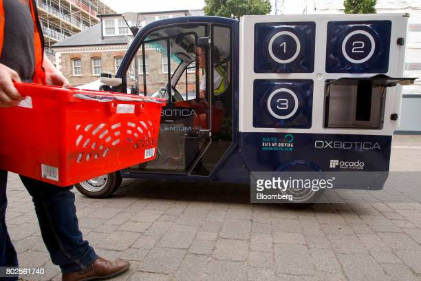 An Ocado Group Plc representative demonstrates a delivery from the CargoPod autonomous grocery delivery vehicle developed by Oxbotica Ltd during...