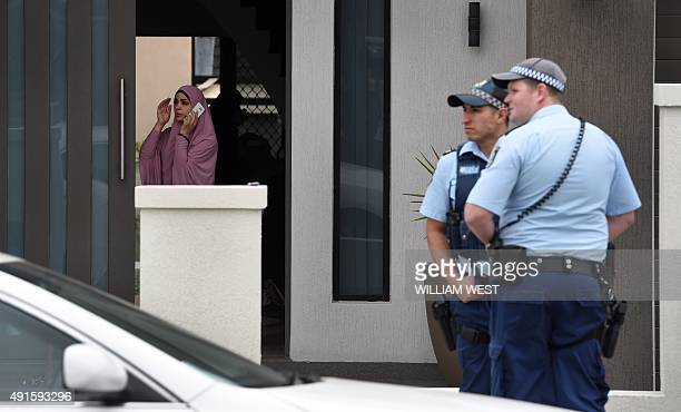 An occupant of a house talks on a phone while police stand guard as four people were arrested over the terrorlinked murder of a police employee after...
