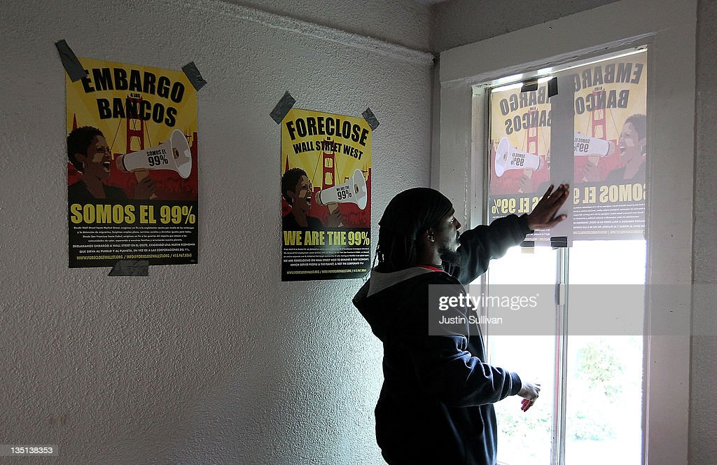 An Occupy protester hangs posters on windows in a foreclosed home that they re-occupied on December 6, 2011 in Oakland, California. Occupy Wall Street groups across the country are staging a day of action against home foreclosures and are protesting outside banks and attempting to re-occupy homes that have been foreclosed.