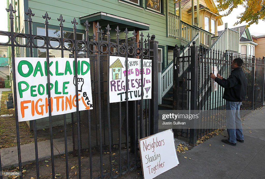 An Occupy protester hangs signs on the gate in front of a foreclosed home that protestors re-occupied on December 6, 2011 in Oakland, California. Occupy Wall Street groups across the country are staging a day of action against home foreclosures and are protesting outside banks and attempting to re-occupy homes that have been foreclosed.
