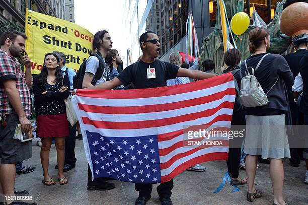 An Occupy Wall Street protester holds an American flag upside down as a sign of distress near Wall Street September 17 2012 on the one year...