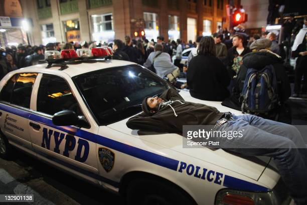 An Occupy Wall Street protester lies on a police car after the police in riot gear removed the protesters the protesters early in the morning from...