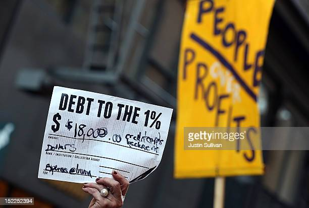 An Occupy Wall Street protestor holds up a mock debt note during a demonstration on September 17 2012 in San Francisco California An estimated 100...