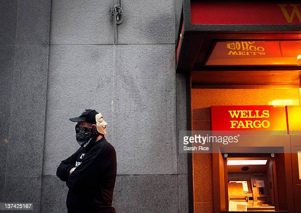 An 'Occupy Wall Street West' protestor from San Francisco California stands near an ATM machine at a Wells Fargo bank in the financial district as...