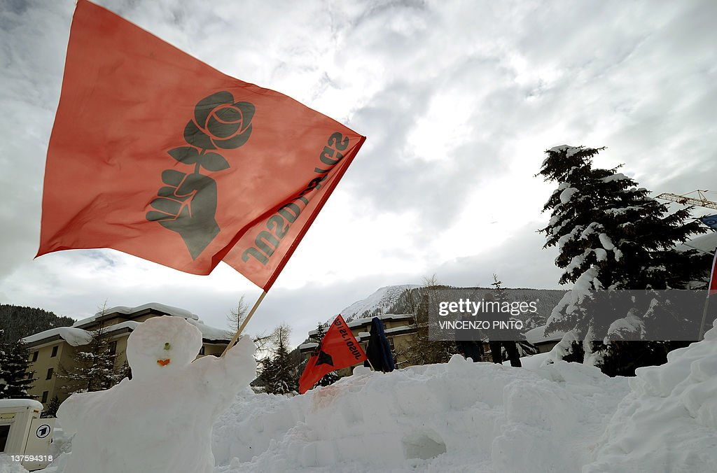 An 'Occupy WEF' flag is displayed on the snow to protest against the World Economic Forum (WEF) at the Swiss resort of Davos on January 23, 2012. Some 1,600 economic and political leaders, including 40 heads of states and governments, will be asked to urgently find ways to reform a capitalist system that has been described as 'outdated and crumbling as they converge at eastern Switzerland's chic ski station of Davos for the 42nd edition of the five-day World Economic Forum (WEF) which opens on January 25, 2012. AFP PHOTO / VINCENZO PINTO