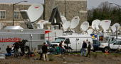 An ocean of satellite dish trucks and media employees work in front of the Virginia Tech Alumni Center April 18 2007 in Blacksburg Virginia Hundreds...