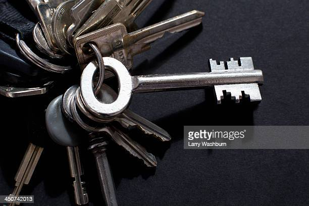 An odd shaped old-fashioned key sticking out from a key ring of various other keys