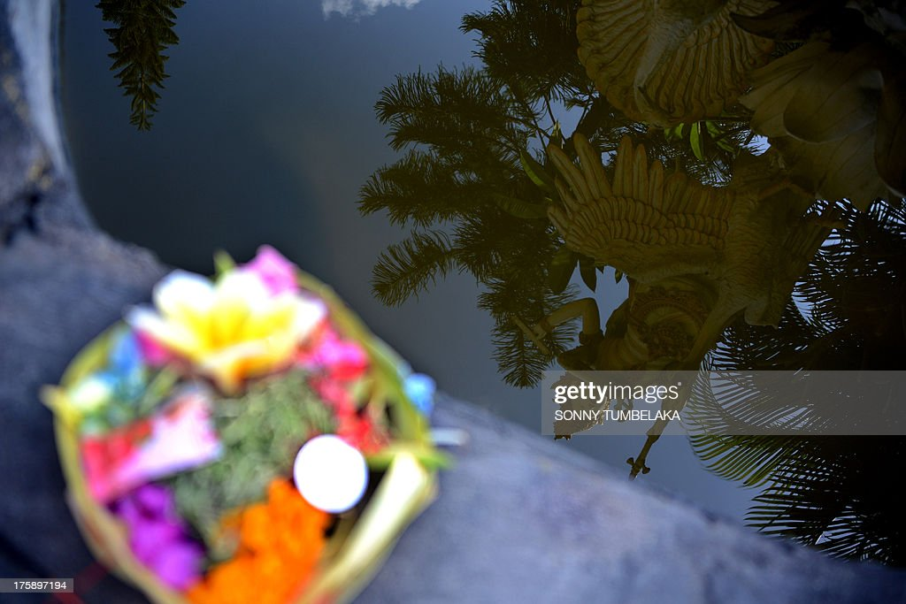 An offering is seen near a Saraswati statue reflected on the water during the Hindu Saraswati holy day at a school in Denpasar on Bali island on August 10, 2013. Hindu devotees in Bali celebrated Saraswati day - the day to worship God in his manifestation as the master of all knowledge.