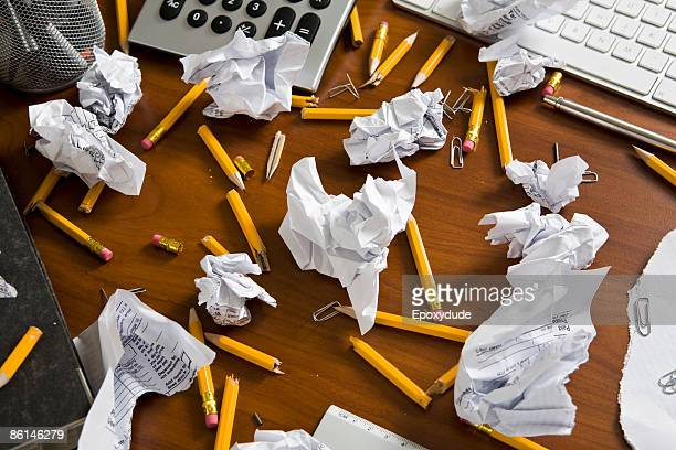 An office desk cluttered with pencils and crumpled paper