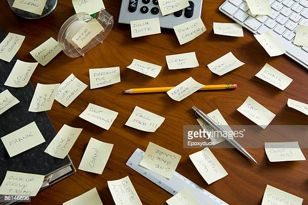 An office desk cluttered with reminders written on adhesive notes