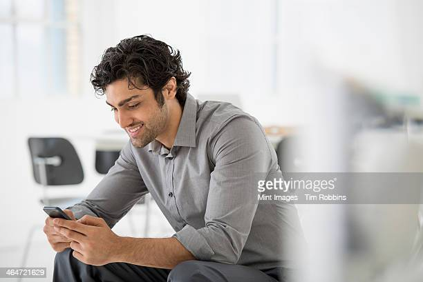 An office in the city. Business. A man seated looking at the screen on his smart phone.