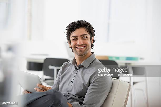 An office in the city. Business. A man seated smiling and holding a digital tablet.