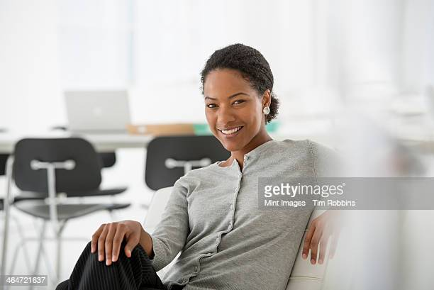 An office in the city. Business. A woman seated on the sofa looking relaxed.