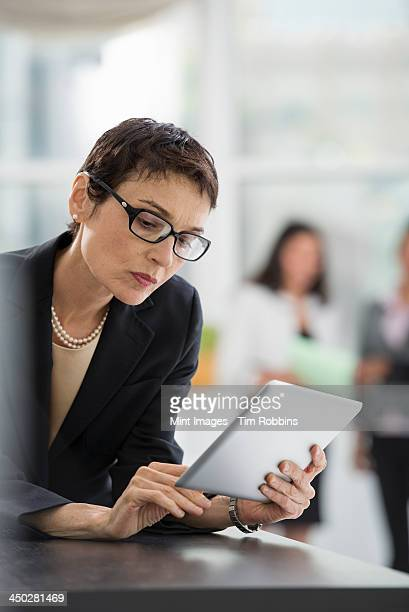 An office interior. A woman in a black jacket using a digital tablet.