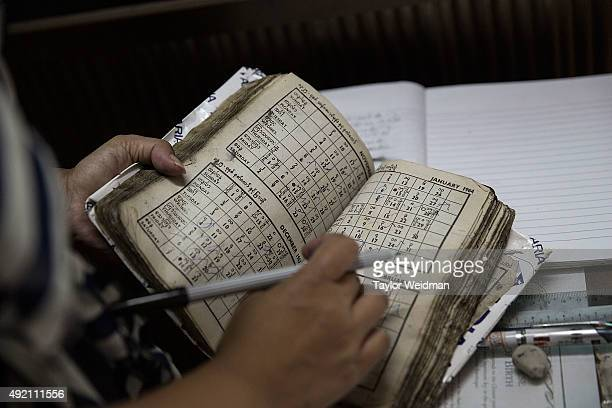 An office worker consults an astrological book at astrologer San Zarni Bo's office on October 10 2015 in Yangon Myanmar Astrology and fortune telling...