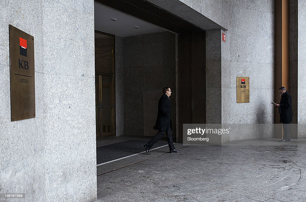 An office worker exits the offices of the Komercni Banka AS bank in the financial district of Prague, Czech Republic, on Tuesday, Jan. 8, 2013. The Czech economy is showing weak domestic demand as households and businesses cut spending due to government austerity programs and the euro area's debt crisis. Photographer: Bartek Sadowski/Bloomberg via Getty Images