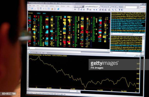 An office worker looks at a screen showing trading on the FTSE 100 index after Investors were rocked today after the credit crunch claimed Lehman...
