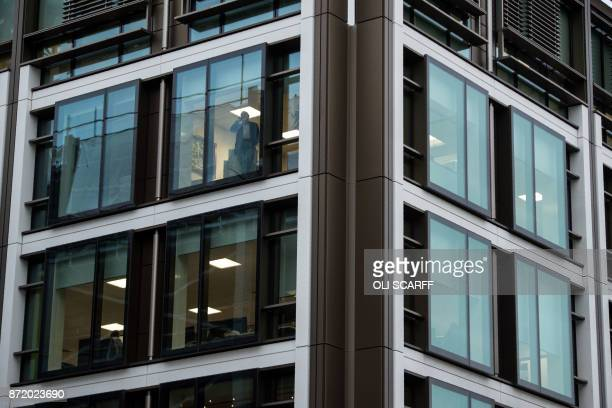 An office worker looks out from the window of the offices of a financial institution in St Helier on the British island of Jersey on November 9 2017...