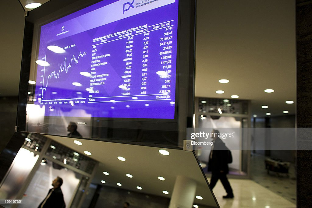 An office worker passes an electronic stock index chart displayed in the Prague Stock Exchange in Prague, Czech Republic, on Tuesday, Jan. 8, 2013. The Czech economy is showing weak domestic demand as households and businesses cut spending due to government austerity programs and the euro area's debt crisis. Photographer: Bartek Sadowski/Bloomberg via Getty Images