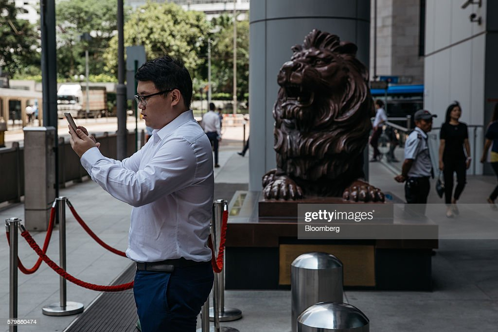 An office worker plays Nintendo Co.'s Pokemon Go augmented-reality game, developed by Niantic Inc., on his smartphone outside the HSBC Holdings Plc headquarters building during lunch hour in Hong Kong, China, on Monday, July 25, 2016. After debuting in the U.S. earlier this month, Pokemon Go launched in Japan on Friday and became available in Hong Kong on Monday. Photographer: Anthony Kwan/Bloomberg via Getty Images
