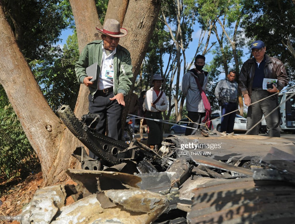 An officer from Department of Civil Aviation inspects the remains of a plane that crash landed the day before near Heho airport in the southern Shan state on December 26, 2012. Myanmar was investigating the cause of an air accident that left two people dead and 11 injured when a passenger jet packed with foreign tourists crash-landed and caught fire. AFP PHOTO/Soe Than WIN