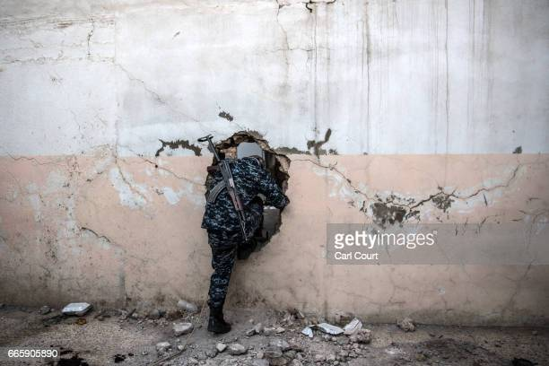 An officer from Mosul police force climbs through a hole in a wall between buildings as he moves to a position overlooking and in range of an Islamic...