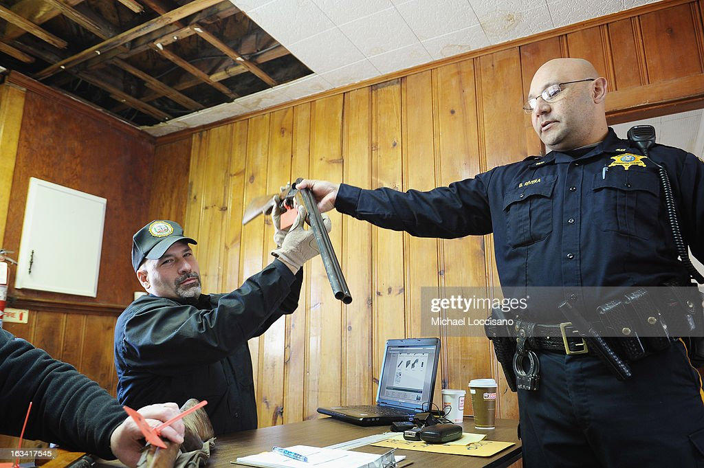 An officer from the Monmouth County Sheriff's Office (R) hands a firearm over to Detective Rocco Santorsola of the Monmouth County Prosecutor's Office during a gun buyback program on March 9, 2013 in Keansburg, New Jersey. In a national effort to curb gun violence, the NJ Attorney General's Office in cooperation with the Monmouth County Prosecutor's Office held an anonymous buyback program where every gun turned in is to be melted down.