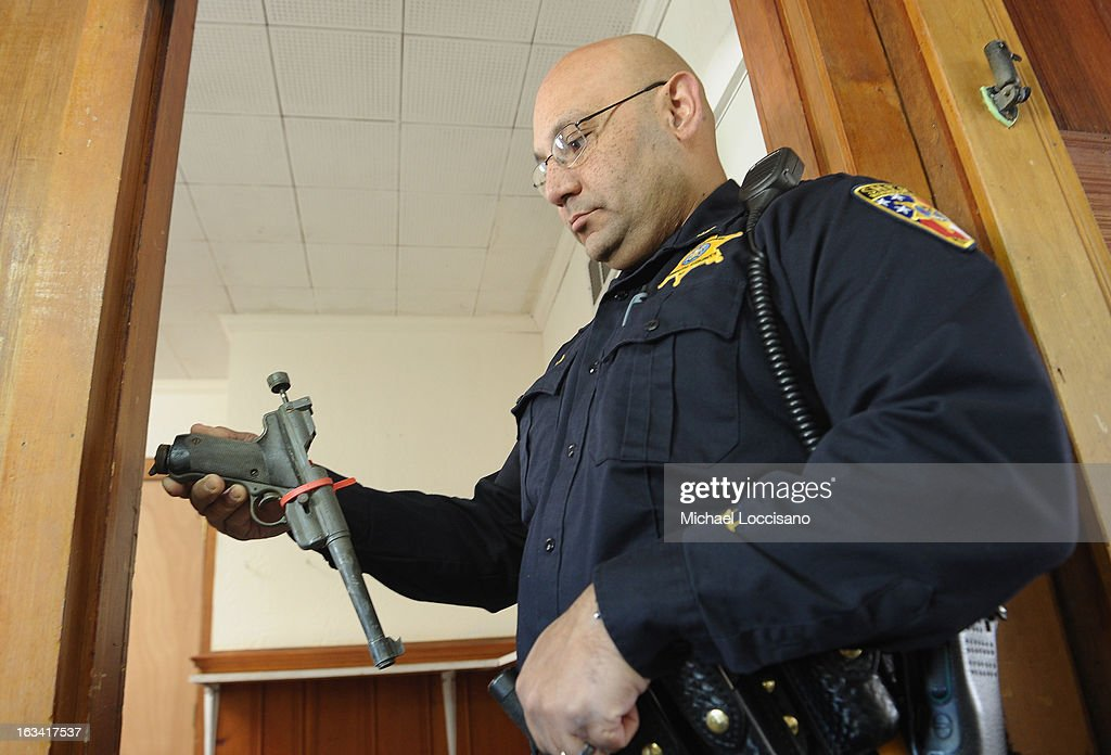 An officer from the Monmouth County Sheriff's Office receives a handgun turned during a gun buyback program on March 9, 2013 in Keansburg, New Jersey. In a national effort to curb gun violence, the NJ Attorney General's Office in cooperation with the Monmouth County Prosecutor's Office held an anonymous buyback program where every gun turned in is to be melted down.