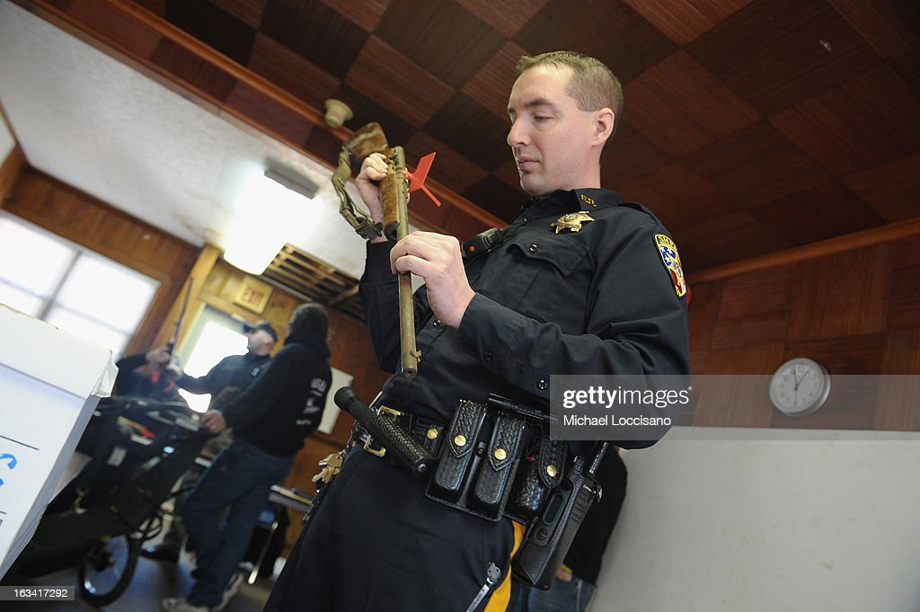 An officer from the Monmouth County Sheriff's Office views a serial number on a firearm turned in during a gun buyback program on March 9, 2013 in Keansburg, New Jersey. In a national effort to curb gun violence, the NJ Attorney General's Office in cooperation with the Monmouth County Prosecutor's Office held an anonymous buyback program where every gun turned in is to be melted down.
