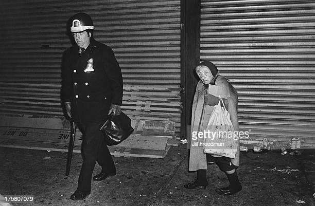 An officer from the NYPD walks next to an elderly homeless woman in Midtown Manhattan New York City 1979