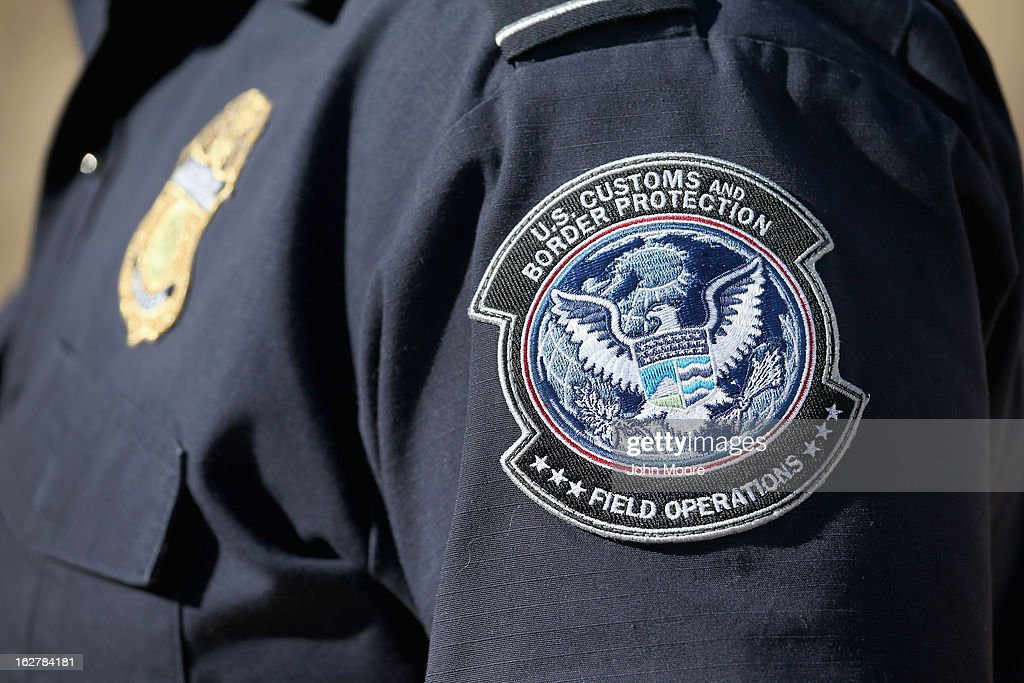 An officer from the U.S. Office of Field Operations (OFO), stands near the U.S.-Mexico border on February 26, 2013 in Nogales, Arizona. Some 15,000 people cross between Mexico and the U.S. each day in Nogales, Arizona's busiest border crossing.