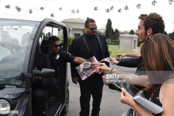 An officer gives memorial service programs to fans and othes after the funeral and memorial service for Soundgarden frontman Chris Cornell May 26...