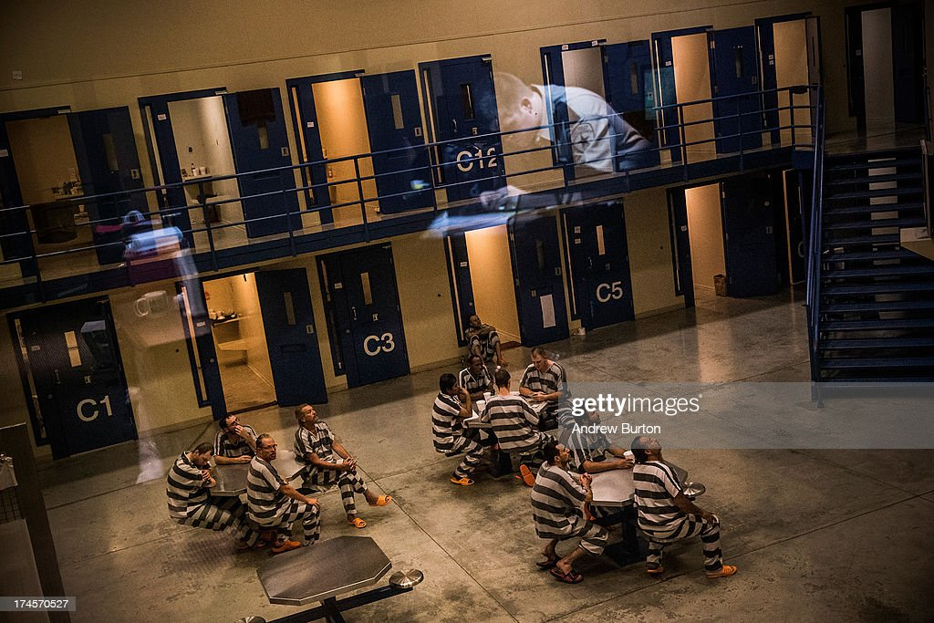 An officer is reflected in the glass as inmates sit in the county jail on July 26, 2013 in Williston, North Dakota. The state has seen a rise in crime, automobile accidents and drug usage recently, due in part to the oil boom which has brought tens of thousands of jobs to the region, lowering state unemployment and bringing a surplus to the state budget.