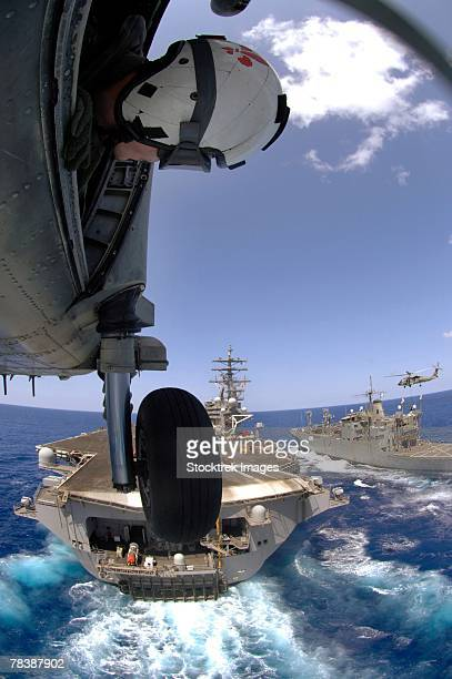 An officer leans out of a SH-60 Seahawk as the helicopter approaches an aircraft carrier.