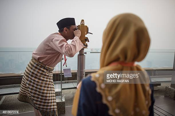An officer of Malaysia's Islamic authority use a Theodolite to perform 'rukyah' the sighting of the new moon of Ramadan on the observation deck of...