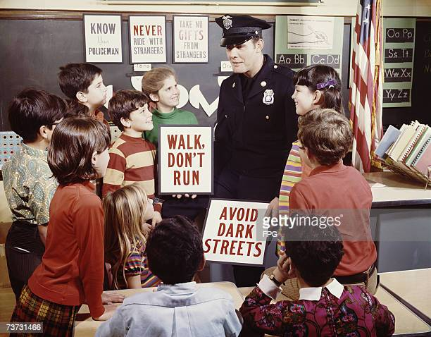 An officer of the Beverly Hills Police Department gives a safety talk to schoolchildren circa 1970
