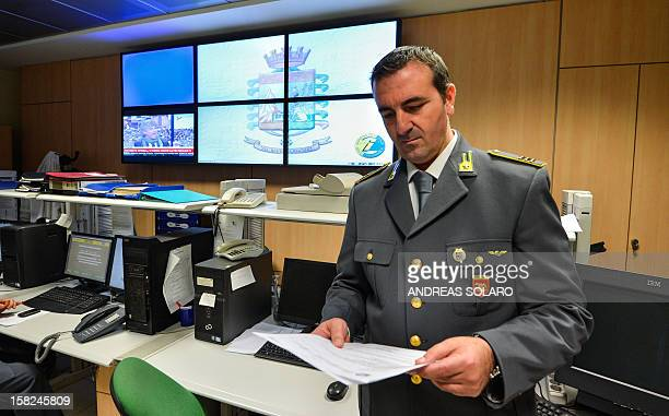 An officer of the Guardia di Finanzia reads a report in the operation room of the regional comando of the Lazio area on November 20 2012 in Rome The...
