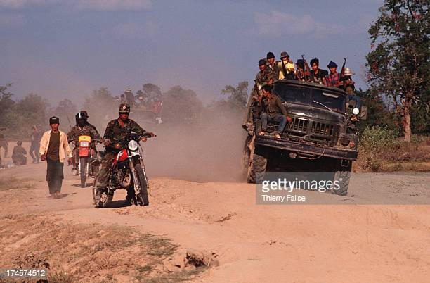 An officer of the guerilla antiPhnom Penh Khmer Peoples National Liberation Front leads a truck full of soldiers to the front line on his motorbike