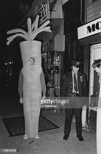 An officer of the NYPD stands next to a man in a carrot costume on Hallowe'en in New York City circa 1979