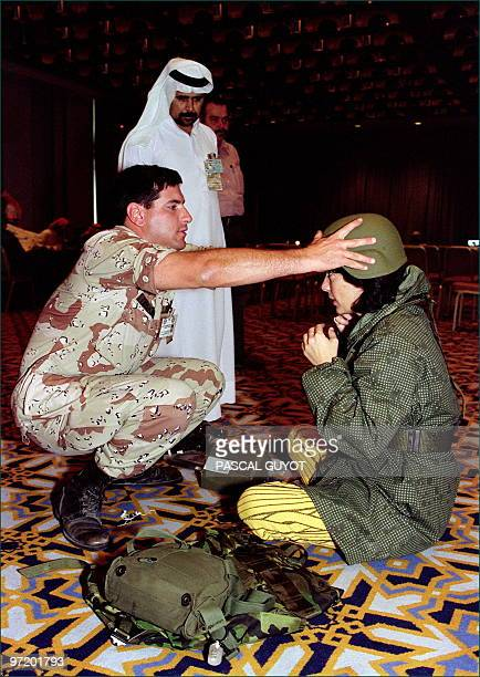 An officer of the US Army adjusts 05 January 1991 in a Dhahran hotel the helmet of Cable News Network star reporter Christiane Amanpour during a...