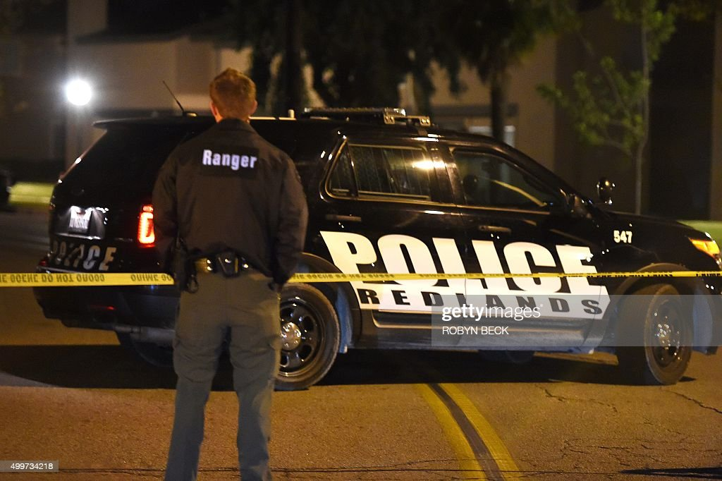 An officer stands guard at the police perimeter in a Redlands California neighborhood where a home linked to the suspects in the San Bernardino...
