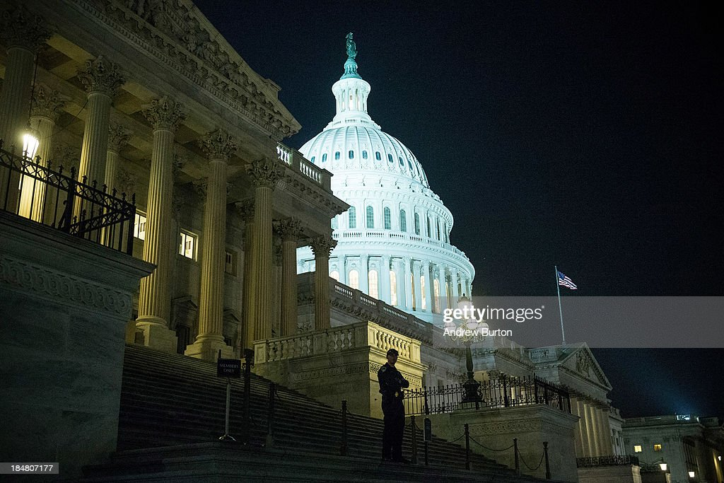 An officer stands on the steps of the House side of the Capitol building after a bipartisan bill passed by the House and the Senate reopened the...