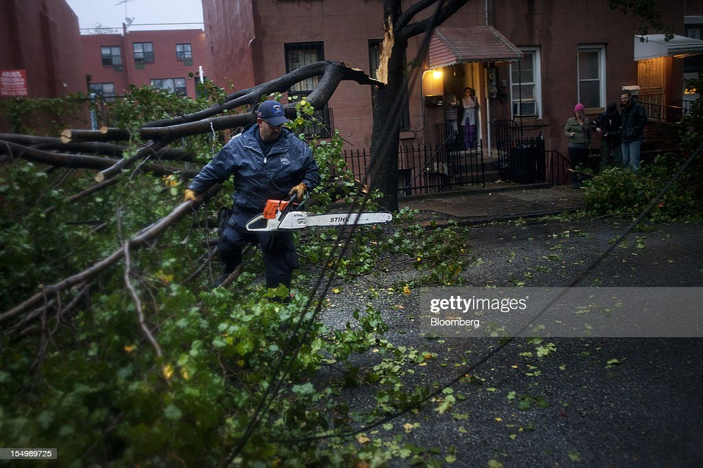 An officer with the New York City Police Department (NYPD) Emergency Services Unit cuts away a fallen tree in the Red Hook neighborhood of Brooklyn in New York, U.S., on Monday, Oct. 29, 2012. Hurricane Sandy, the Atlantic's Ocean's biggest-ever tropical storm, barreled toward southern New Jersey after bringing a region with 60 million residents to a virtual standstill and upending the U.S. presidential race eight days before Election Day. Photograph: Victor J. Blue/Bloomberg via Getty Images