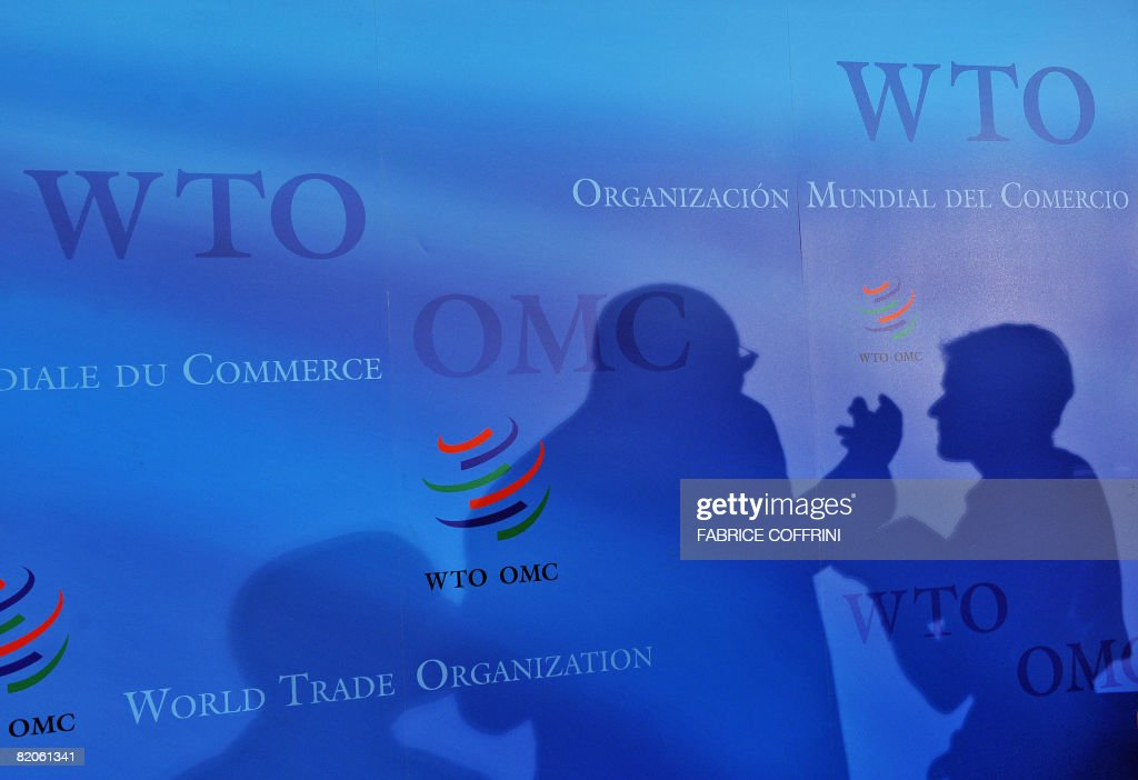 An official and journalist are seen in silhouette after a press conference during World Trade Organisation talks on July 25 2008 at the WTO...