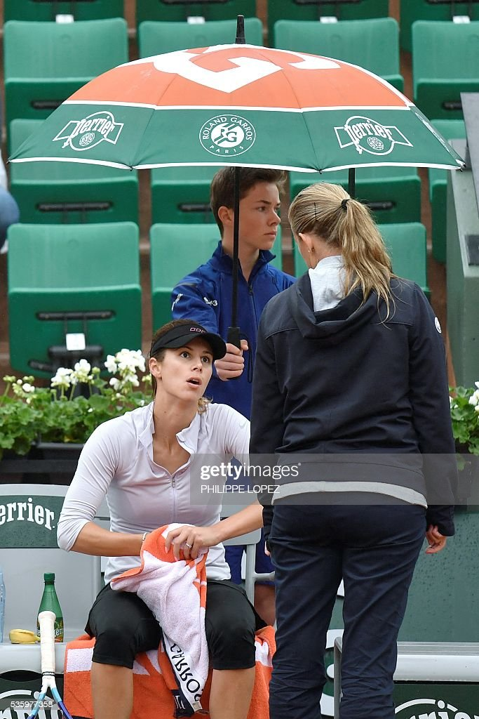 An official announces to Bulgaria's Tsvetana Pironkova play is interrupted due to rain during herr women's fourth round match against Poland's Agnieszka Radwanska at the Roland Garros 2016 French Tennis Open in Paris on May 31, 2016. / AFP / PHILIPPE
