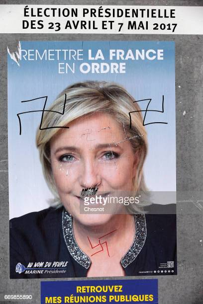 An official campaign poster graffitied with a Nazi Swastika of Marine Le Pen French National Front political party leader and one of the eleven...