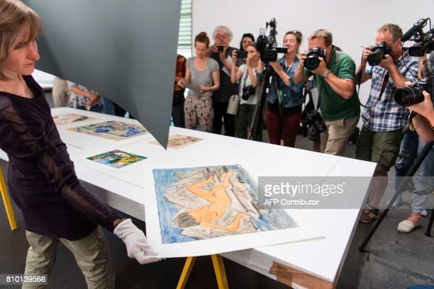 An official diplays the 'Otto Mueller Liegende weiblicher Akt am Wasser OJ Aquarell Kunstmuseum Bern Legat Cornelius Gurlitt 2014' during a press...